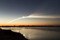 Dymny ślad od rakiety przy zmierzchem z odbiciem w wodzie fotografia stock