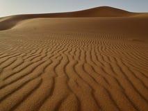 Dyn och vågor av sand av den Sahara öknen, i bakgrund ett stort berg av sand, Merzouga, Marocko Arkivfoto