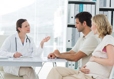 Dynaecologist discussing with expectant couple Royalty Free Stock Image