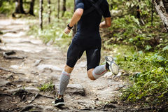 Dynamic athlete running marathon in woods. Legs in compression socks stock photography