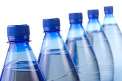 Dynamic bottles. Five blue plastic bottles dynamic view on white background, focus on the first Royalty Free Stock Images