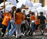Dynamic and cheerful students dance with white umbrellas Royalty Free Stock Photo