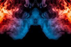 A dynamic explosion of puffs of smoke of light blue pink and red. Colors on a black background with smooth flames rendering an isolated pattern. Decorative stock photography