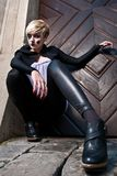 Dynamic fashion model pose. Young dynamic model dressed in black with short blond hair, wide angle shoot. High fashion styling and makeup royalty free stock images