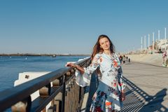 Dynamic fashion style Portrait of a young beautiful girl walking along the waterfront of the city stock images