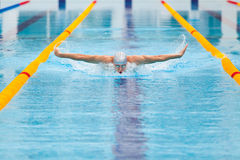 Dynamic and fit swimmer in cap breathing performing the butterfly stroke Royalty Free Stock Photos