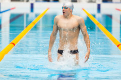 Dynamic and fit swimmer in cap breathing performing jumping out the water, concept of victory, freedom, happiness Royalty Free Stock Photography
