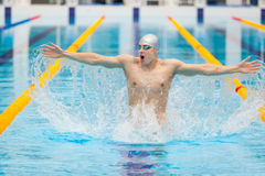 Dynamic and fit swimmer in cap breathing performing jumping out the water, concept of victory, freedom, happiness Stock Image