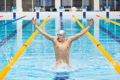 Dynamic and fit swimmer in cap breathing performing jumping out the water, concept of victory, freedom, happiness Stock Photos