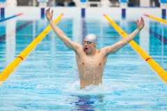 Dynamic and fit swimmer in cap breathing performing jumping out the water, concept of victory, freedom, happiness Royalty Free Stock Photo