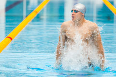 Dynamic and fit swimmer in cap breathing performing jumping out the water, concept of victory, freedom, happiness. Healthy lifestyle Royalty Free Stock Photo