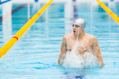 Dynamic and fit swimmer in cap breathing performing jumping out the water, concept of victory, freedom, happiness Royalty Free Stock Photos