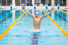 Dynamic and fit swimmer in cap breathing performing jumping out the water, concept of victory, freedom, happiness. Healthy lifestyle Royalty Free Stock Photos