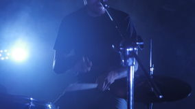 Dynamic footage with a male drummer plays on a drum set. A shot from a music video of rock, pop, heavy metal, punk band. A dynamic video with a male drummer stock footage