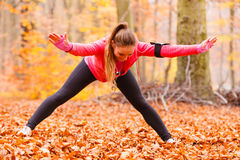 Dynamic girl stretching in forest. Stock Photos