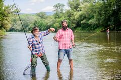 Dynamic Hobbies. two happy fisherman with fishing rod and net. Camping on the shore of lake. hunting tourism. father and