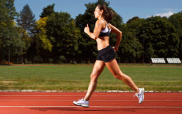Dynamic image of a young woman running on a track. Shot in location with studio lights Royalty Free Stock Images