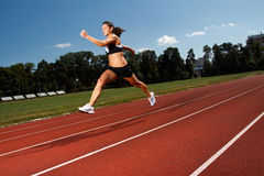 Dynamic image of a young woman running on a track Royalty Free Stock Photo