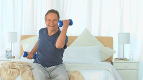 Dynamic man with dumbbells Stock Images