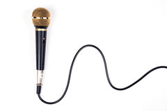 A dynamic microphone. A dynamic mic with a curled cable over on white Royalty Free Stock Image