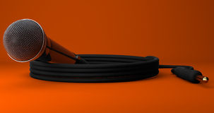 Dynamic Microphone Coiled Lead Jack Plug Orange Background. Dynamic Microphone Coiled Lead Jack Plug Closeup on Orange Background Royalty Free Stock Photography