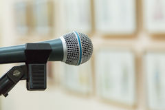 Dynamic microphone at the event. Exhibition hall, paintings on the walls. Focus on foreground, blurred background, bokeh Royalty Free Stock Photo