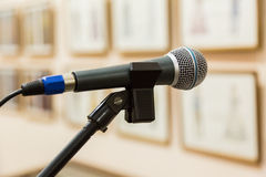 Dynamic microphone at the event. Exhibition hall, paintings on the walls. Focus on foreground, blurred background, bokeh Royalty Free Stock Images
