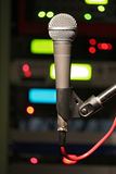 Dynamic Microphone in Studio. A dynamic microphone on a stand in a dark studio with LEDs in the backround Royalty Free Stock Photo