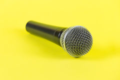 Dynamic microphone on yellow background. Mic Royalty Free Stock Photo