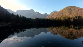 Dynamic moving at Laghi di Fusine lake with reflection of Alps mountains on calm water stock video