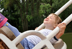 A dynamic outdoor portrait of a smiling little girl on a swing Stock Photography