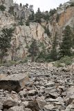 Dynamic Rock Slide. From the bottom of the sheer cliff in which if fell.  Ponderosa pine and piñon  pine are found in the distance Stock Photo