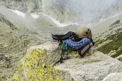 Dynamic rope, helmet, carabiners, climbing harness and descender on the rock Stock Image