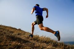 Dynamic running uphill. On trail male athlete runner side view royalty free stock photo
