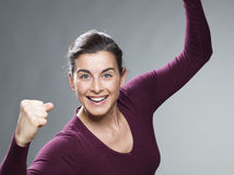 Dynamic 30s woman glowing from within with hands up Royalty Free Stock Image