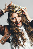 Dynamic smiling woman in golden crown with pearls. In leather jacket stock photography