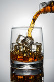 Whiskey with ice, dynamic splash in a glass. Dynamic splash in a glass. Whiskey Royalty Free Stock Photos