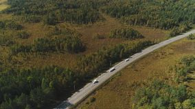 Dynamic top view of green forest, driving cars on sunny afternoon. Dynamic top view of green forest, driving cars on sunny afternoon, trees, road with stock video