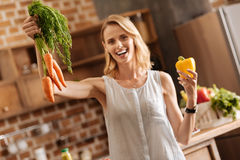 Dynamic vibrant lady holding some veggies in her hands. Energetic lady. Wonderful energetic passionate woman standing in the kitchen and choosing ingredients for Stock Image