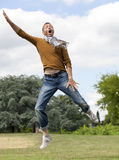 Dynamic young man jumping for fun in green sunny park Royalty Free Stock Photography