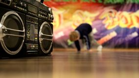 Dynamically dancing boy breakdance. A breakdance steps on the background of graffiti and a cool boobox stock video footage