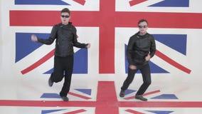 Dynamiczni faceci z okularami przeciwsłonecznymi i czarnymi rzemiennymi motocykl kurtkami tanczą zbiory