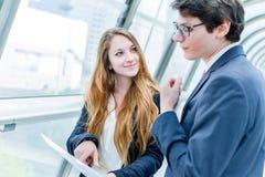 Dynamique junior de cadres consultant les documents commerciaux Images stock