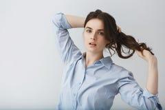 Dynamisch portret die van knappe donkerbruine jonge vrouw die haar haar met handen losmaken, in camera met ontspannen kijken stock foto