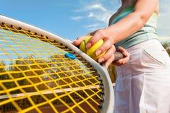 Dynamisch tennisconcept met de vrouwelijke bal van de spelerholding en racke Royalty-vrije Stock Afbeeldingen