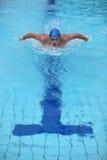 Dynamische en geschikte zwemmer die de vlinderslag uitvoeren Stock Foto's