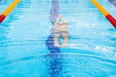 Dynamische en geschikte zwemmer die in GLB uitvoerend de vlinderslag ademen stock afbeeldingen