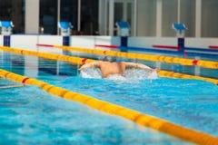 Dynamische en geschikte zwemmer die in GLB uitvoerend de vlinderslag ademen royalty-vrije stock foto