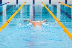 Dynamische en geschikte zwemmer die in GLB uitvoerend de vlinderslag ademen stock foto