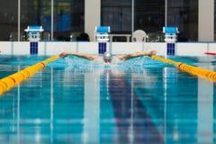 Dynamische en geschikte zwemmer die in GLB uitvoerend de vlinderslag ademen stock fotografie